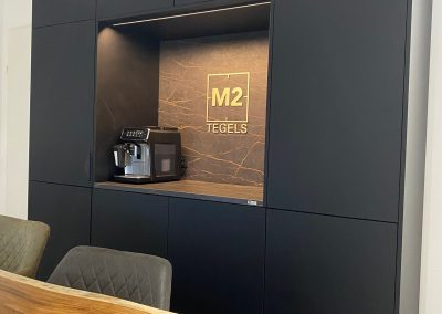 Mat zwarte pantry met Dekton werkblad en achterwand in de showroom van M2 Tegels te Amersfoort