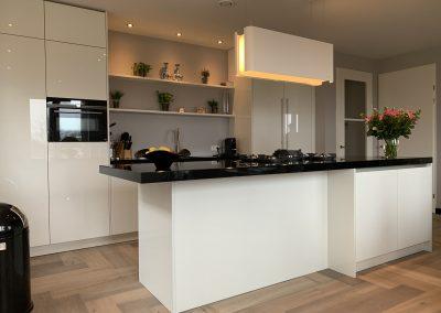 Moderne hoogglans witte eiland keuken met graniet in Leusden